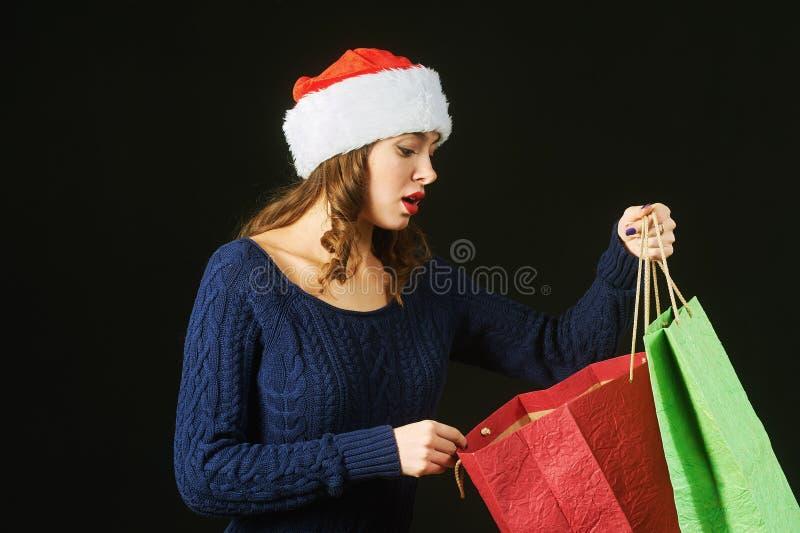 Belle jeune femme gaie dans le chapeau de Santa Claus avec des paquets sur un fond foncé photos stock