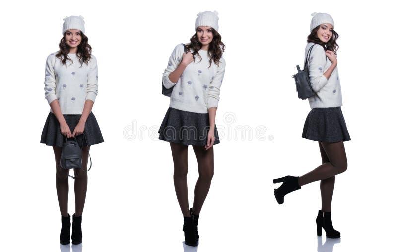 Belle jeune femme gaie utilisant le chandail, la jupe, le chapeau et le sac à dos tricotés D'isolement sur le fond blanc images libres de droits