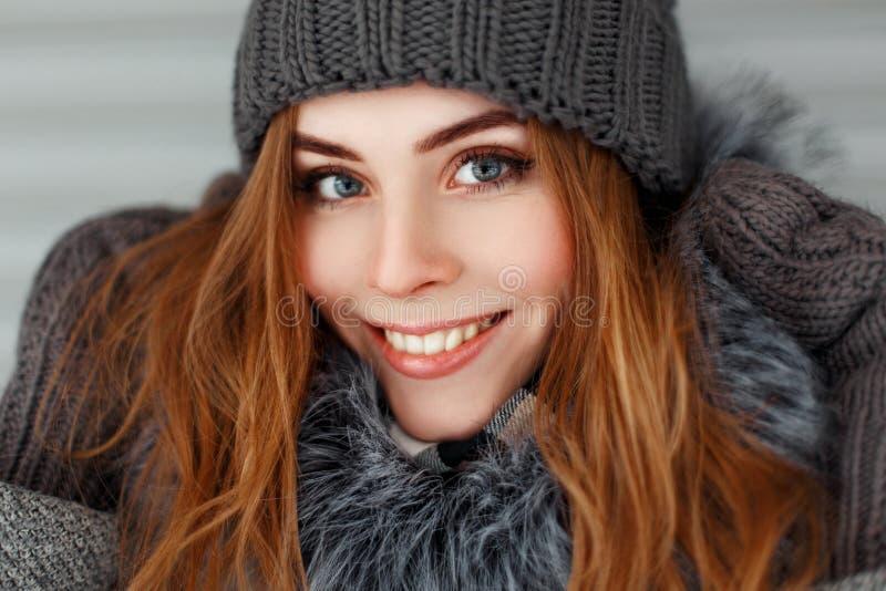 Belle jeune femme heureuse avec un sourire pendant l'hiver tricotée photos libres de droits