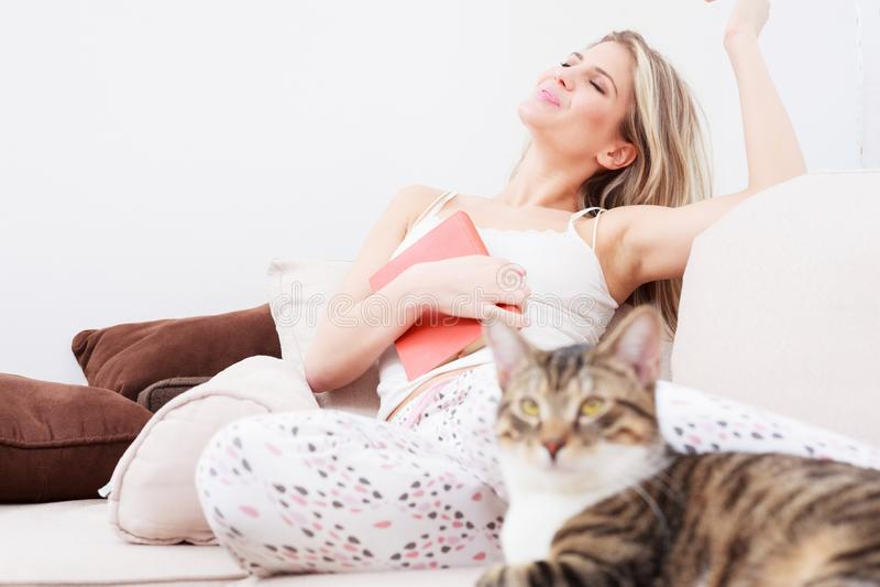 Belle jeune femme heureuse détendant avec les yeux fermés sur un sofa images libres de droits