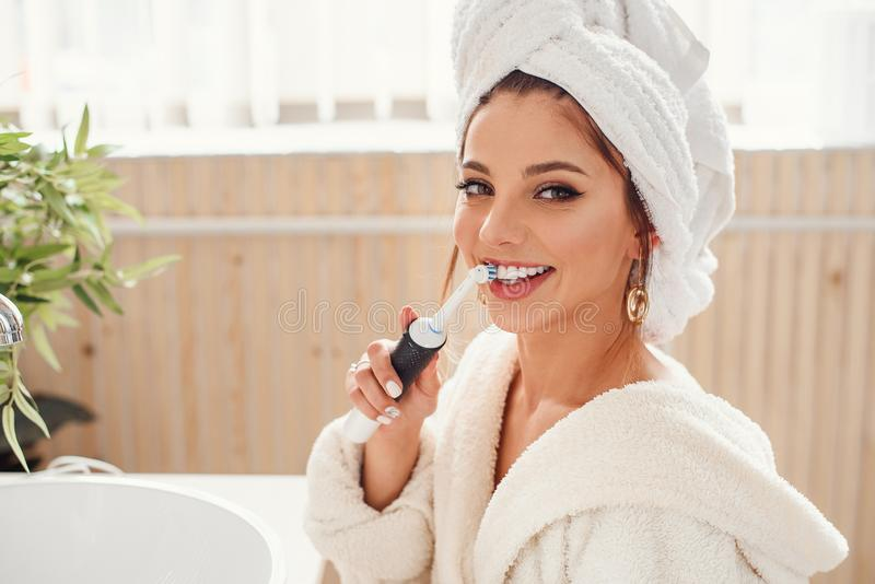 Belle jeune femme heureuse dans la salle de bains confortable avec avec la brosse ? dents dans la main Beaut? et concept de soin  image stock