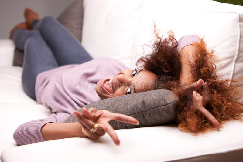 Belle jeune femme heureuse noire sur un sofa image libre de droits