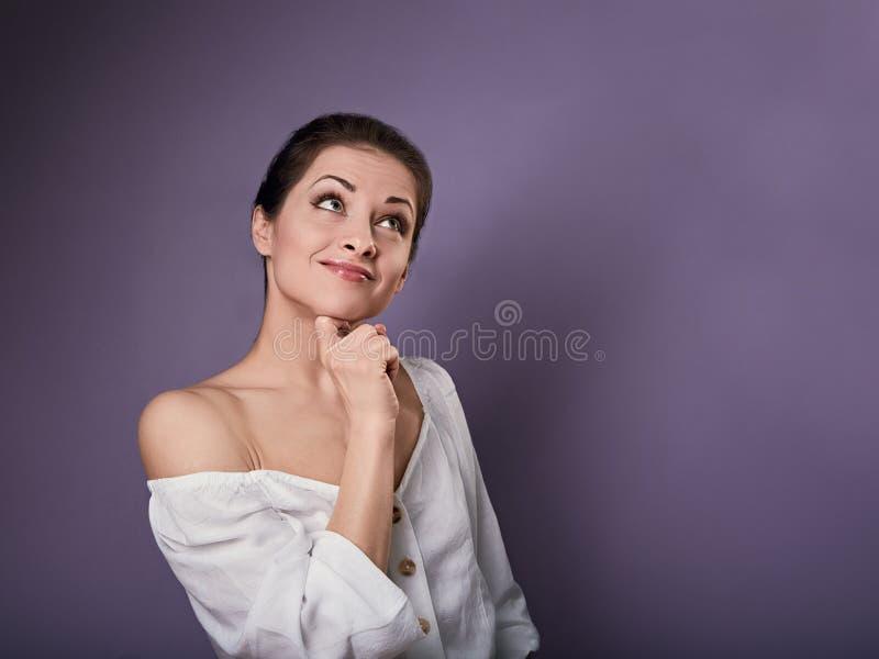 Belle jeune femme heureuse positive avec la main sous le visage imaginant et regardant dans la chemise occasionnelle sur le fond  photo libre de droits