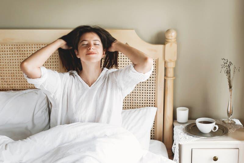 Belle jeune femme heureuse se trouvant sur le lit pendant le matin dans la chambre à coucher de chambre d'hôtel ou à la maison Fi photographie stock