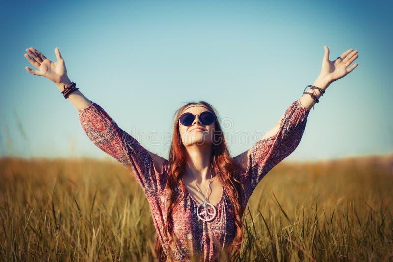 Belle jeune femme hippie s'asseyant dans un domaine et priant à Dieu photographie stock libre de droits