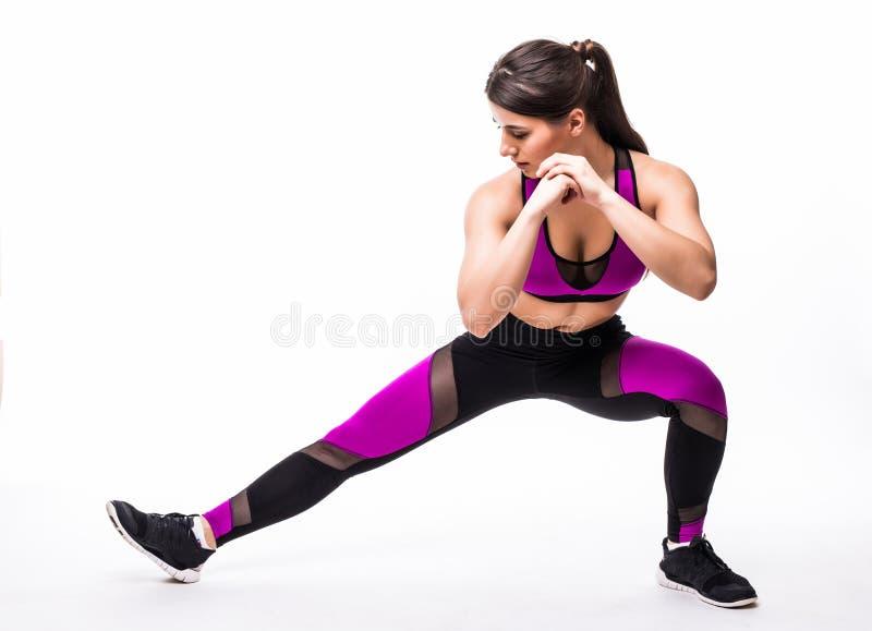 Belle jeune femme hispanique faisant l'exercice de mouvement brusque dans le gymnase de forme physique au-dessus du fond blanc images libres de droits