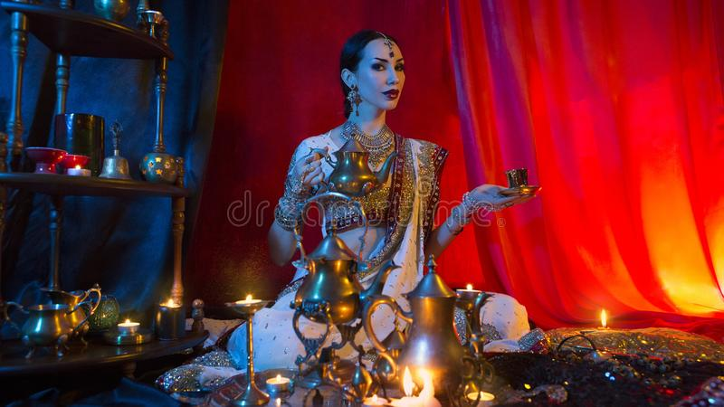 Belle jeune femme indienne dans l'habillement traditionnel de Sari avec le thé se renversant de bijoux orientaux dans la tasse Je image stock