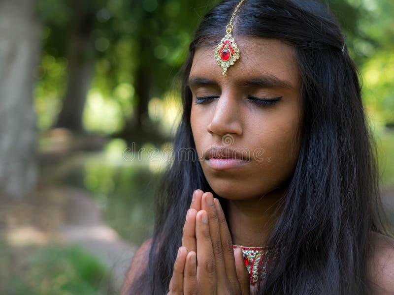 Belle jeune femme indienne priant en parc image stock