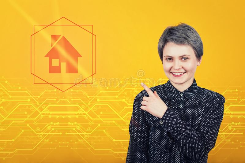 Belle jeune femme indiquant l'index loin, montrant la maison numérique sur l'icône Technologie moderne, concept d'assurance des b photos stock