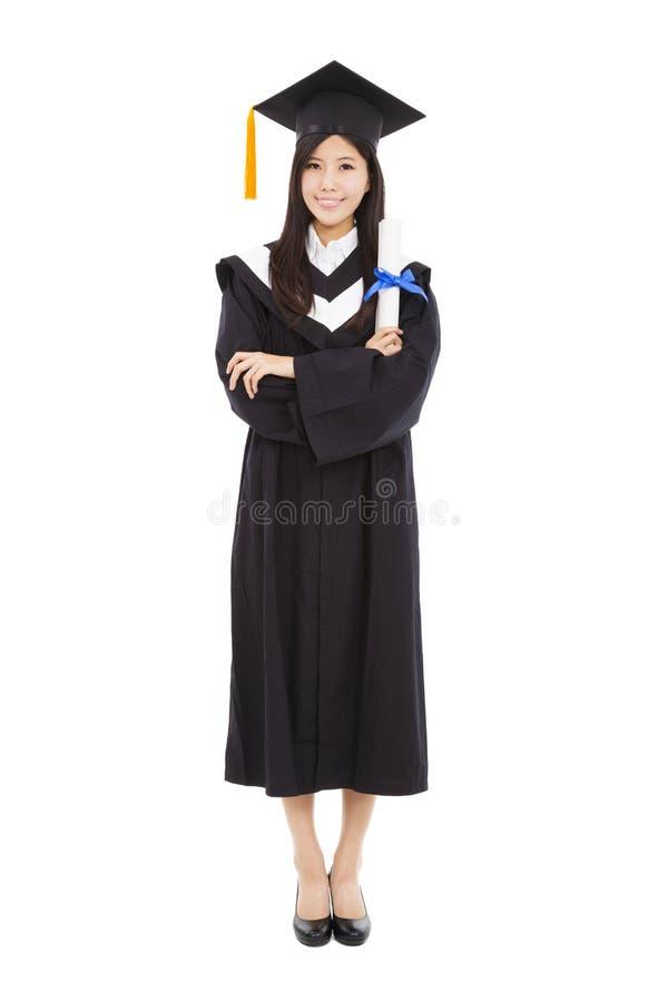 Belle jeune femme d'obtention du diplôme se tenant avec l'isola photos stock