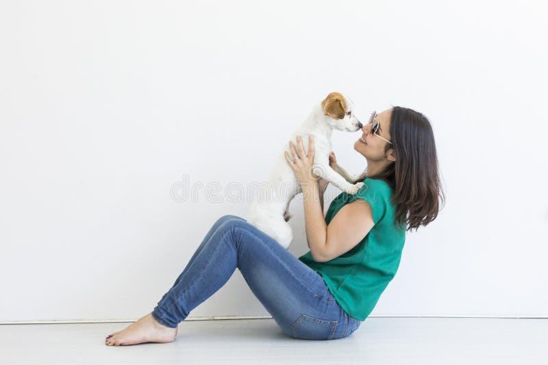 Belle jeune femme jouant avec son petit chien mignon à la maison Portrait de mode de vie Amour pour le concept d'animaux Fond bla images stock