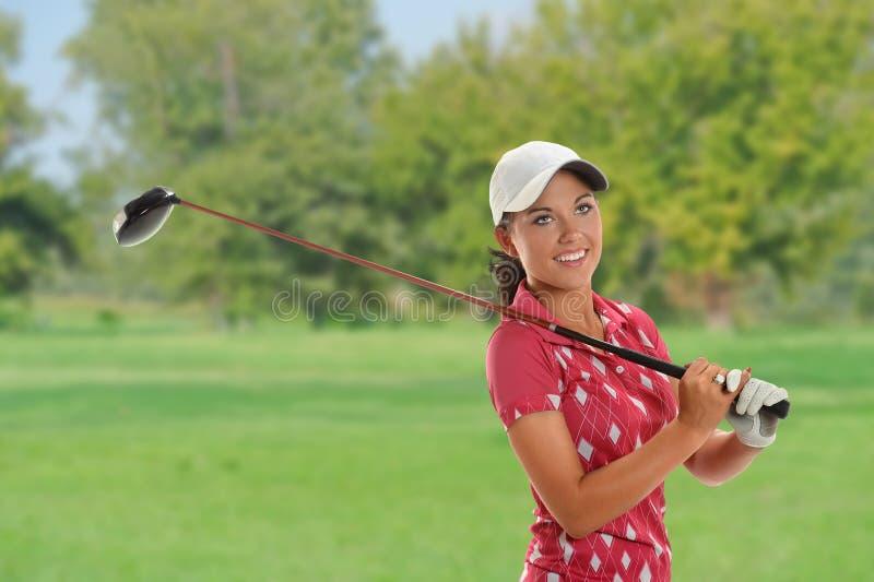 Belle jeune femme jouant le golf photo stock