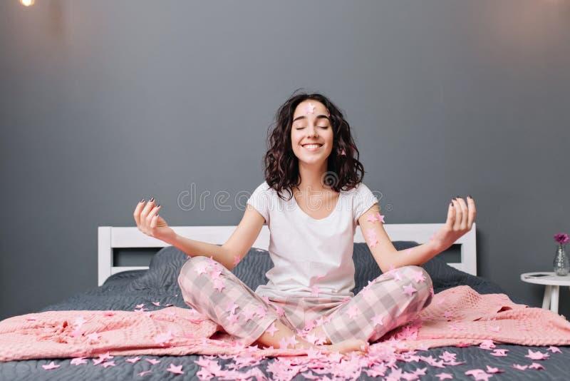 Belle jeune femme joyeuse dans des pyjamas avec les cheveux bouclés de brune méditant sur le lit en tresses roses Sourire modèle  photos libres de droits