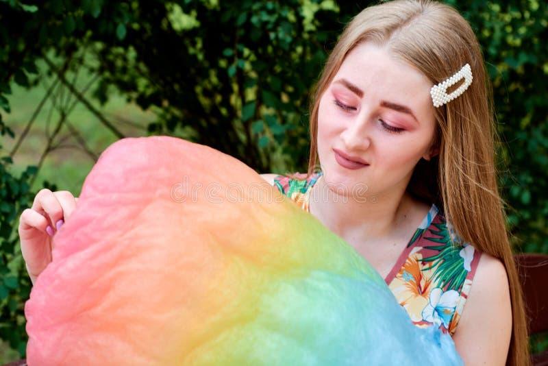Belle jeune femme joyeuse heureuse avec la soie de sucrerie en parc à l'été photographie stock