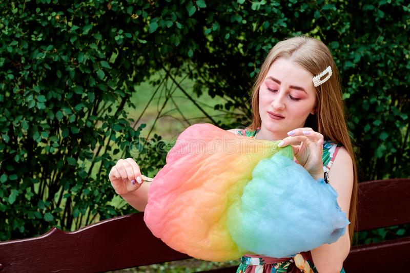 Belle jeune femme joyeuse heureuse avec la soie de sucrerie en parc à l'été photos stock