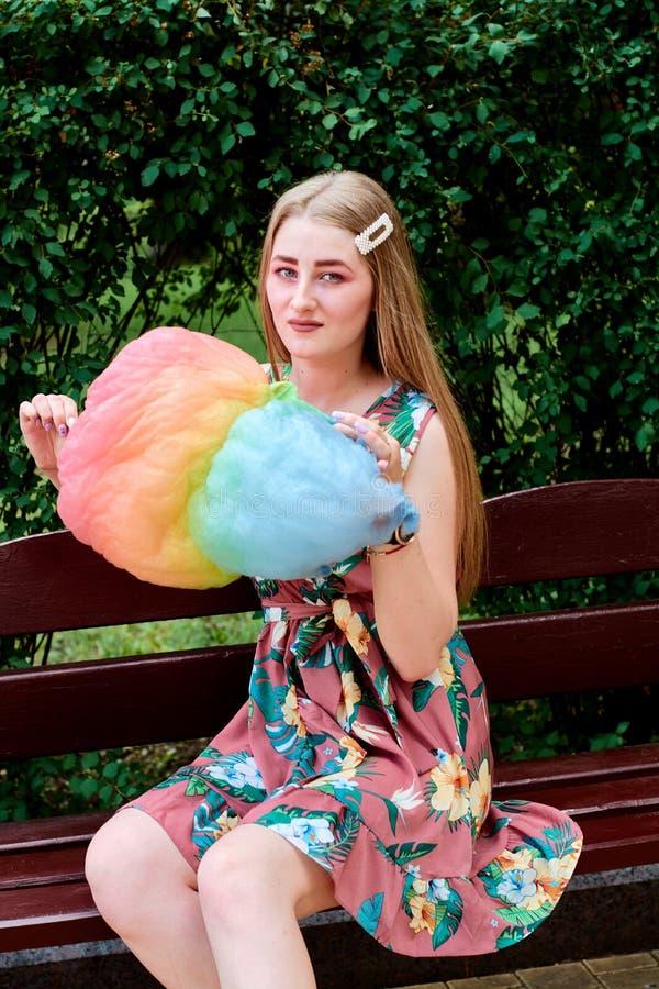 Belle jeune femme joyeuse heureuse avec la soie de sucrerie en parc à l'été images libres de droits