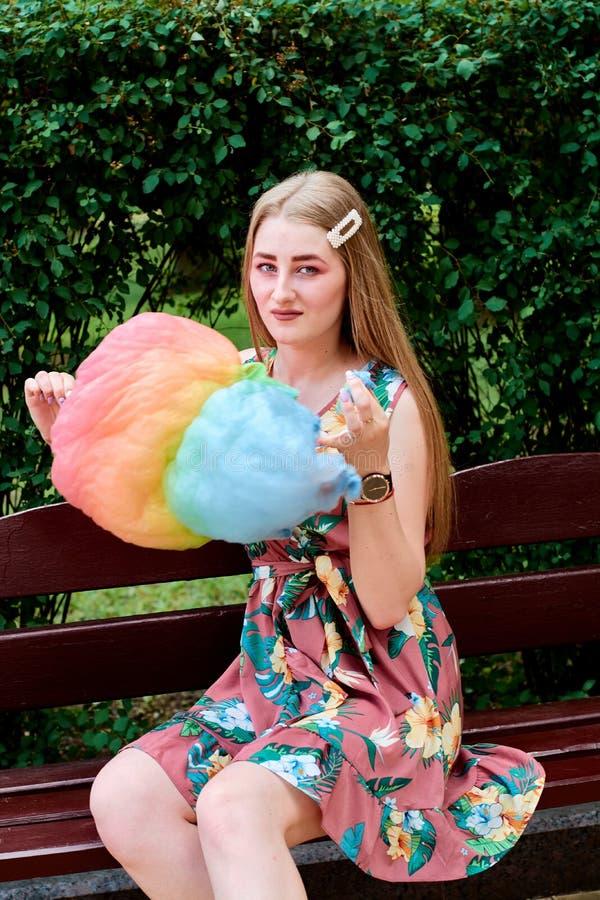 Belle jeune femme joyeuse heureuse avec la soie de sucrerie en parc à l'été image libre de droits