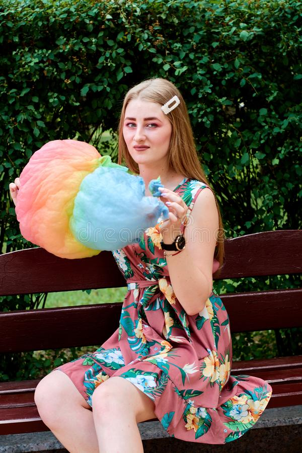 Belle jeune femme joyeuse heureuse avec la soie de sucrerie en parc à l'été images stock