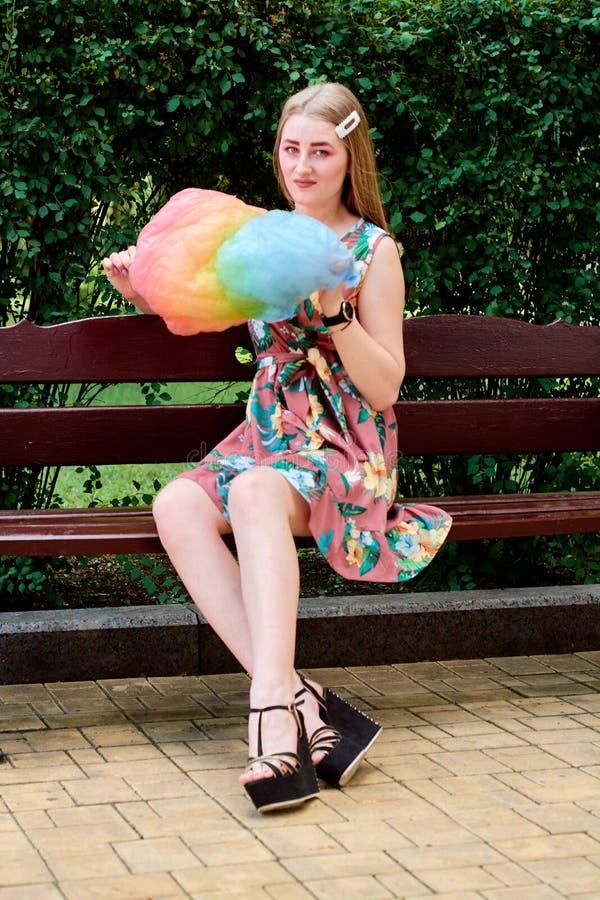 Belle jeune femme joyeuse heureuse avec la soie de sucrerie en parc à l'été photo libre de droits