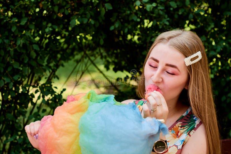 Belle jeune femme joyeuse heureuse avec la soie de sucrerie en parc à l'été photos libres de droits