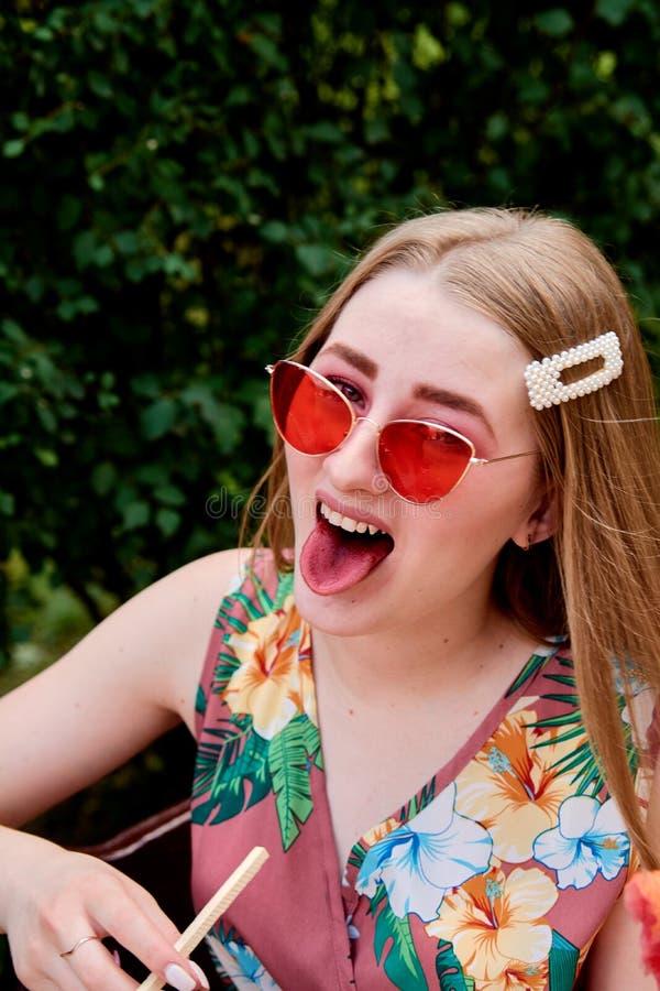 Belle jeune femme joyeuse heureuse avec la soie de sucrerie en parc à l'été photographie stock libre de droits