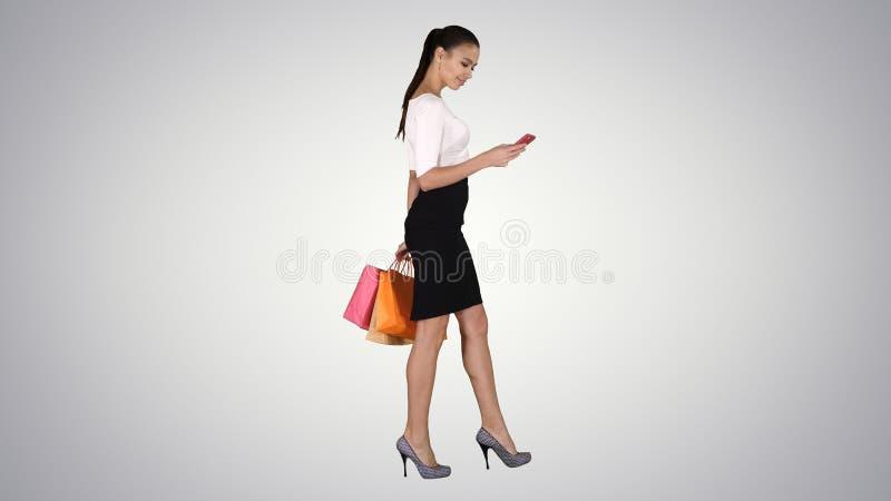 Belle jeune femme ? l'aide d'un t?l?phone portable marchant et tenant des sacs ? provisions sur le fond de gradient images stock