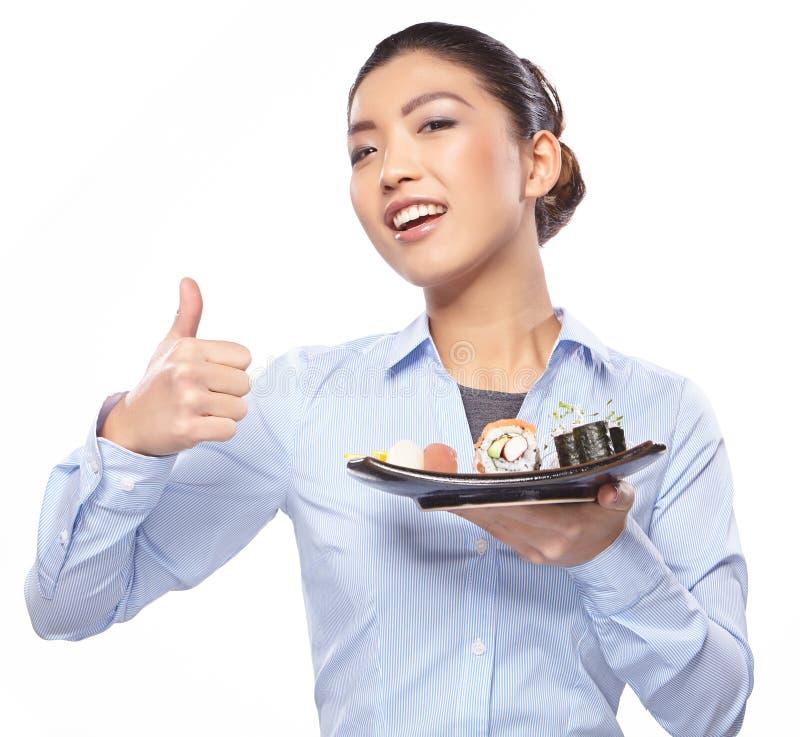 Belle jeune femme mangeant des sushi. photos stock