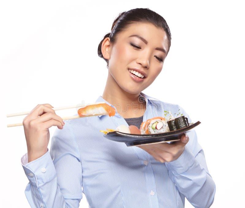 Belle jeune femme mangeant des sushi. photo stock