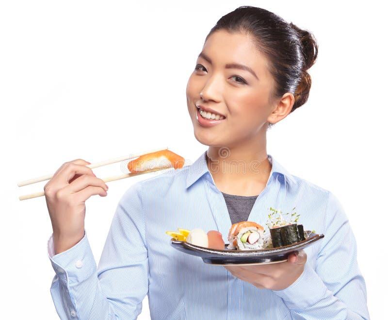 Belle jeune femme mangeant des sushi. image libre de droits