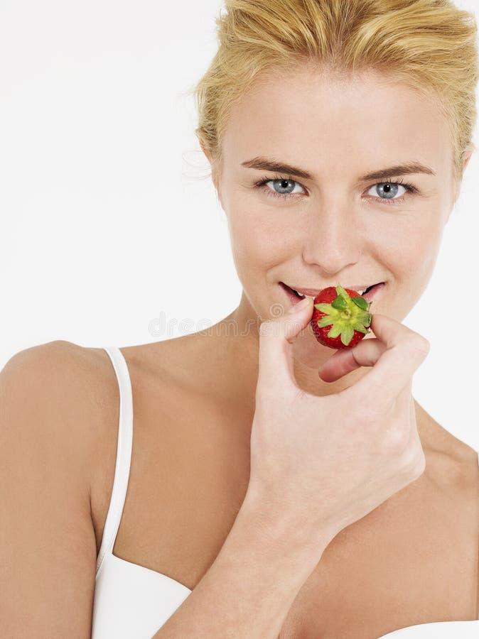 Belle jeune femme mangeant la fraise photos libres de droits