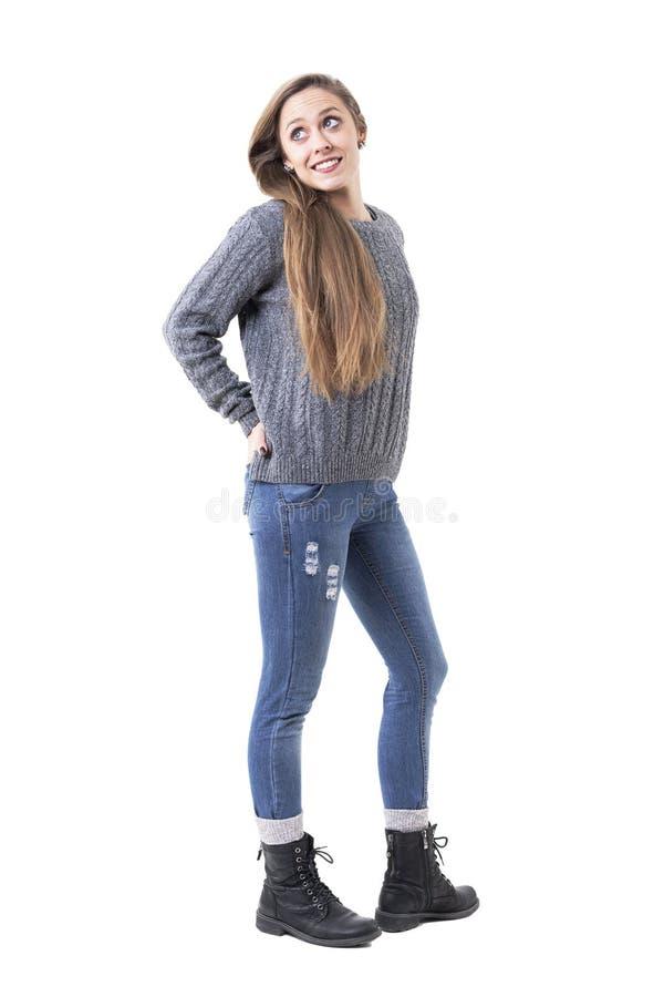 Belle jeune femme mignonne dans le chandail gris de tricots avec des mains dans des poches recherchant au-dessus de l'épaule photo libre de droits