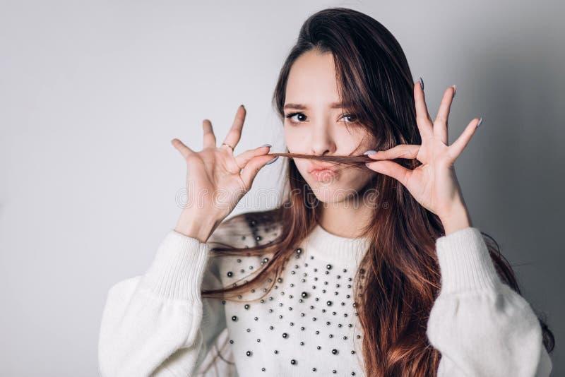 Belle jeune femme mignonne faisant la moustache avec ses cheveux au-dessus du fond blanc La fille fait un visage qui montre des é images stock
