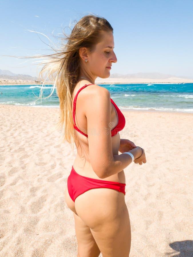 Belle jeune femme mince avec de longs cheveux dans petit bikiniposing sur la plage sablonneuse contre la mer calme Fille d?tendan image libre de droits