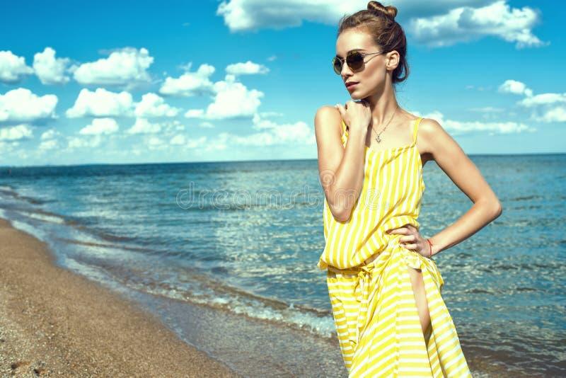 Belle jeune femme mince se tenant au bord de la mer et regardant de côté image stock
