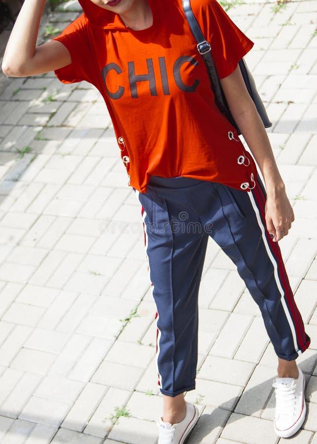Belle jeune femme modèle dans la chemise rouge avec le capot et le trou bleu photo stock