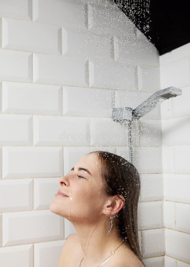 Belle jeune femme nue prenant la douche dans la salle de bains photos stock