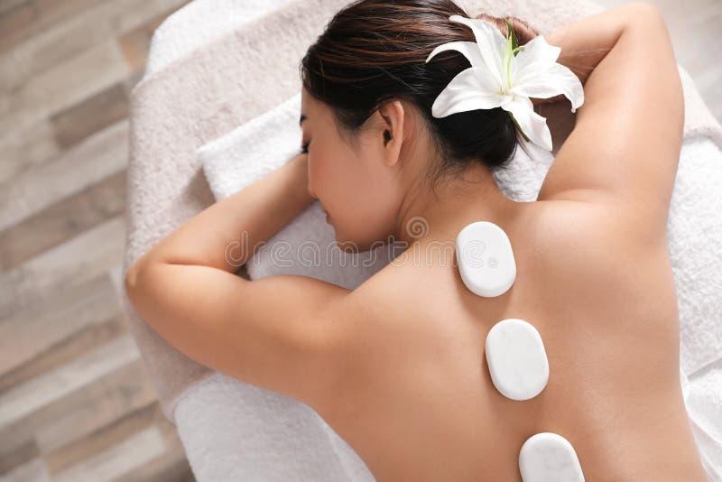 Belle jeune femme obtenant le massage en pierre chaud dans le salon de station thermale photographie stock