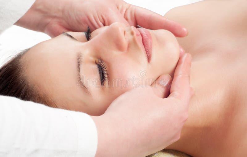 Belle jeune femme obtenant un massage de visage photographie stock libre de droits