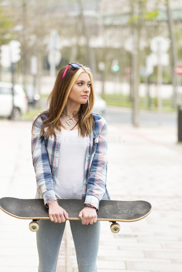 Belle jeune femme occasionnelle avec la planche à roulettes, mode de vie urbain image libre de droits
