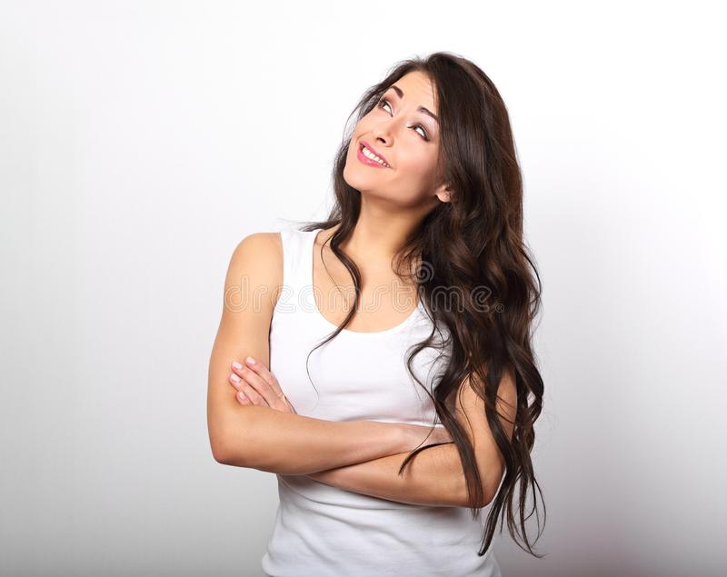 Belle jeune femme occasionnelle positive avec la pensée pliée de bras photos libres de droits