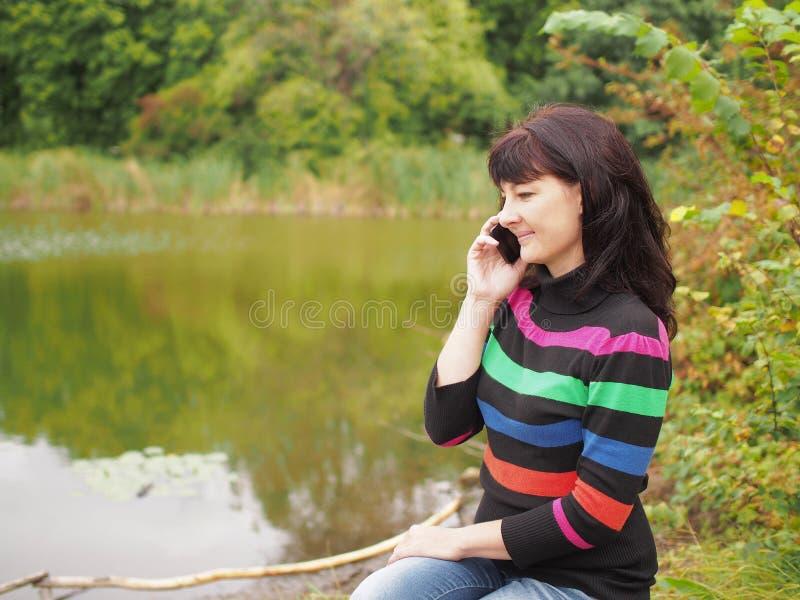 Belle jeune femme parlant au téléphone intelligent au parc d'automne Pré photographie stock