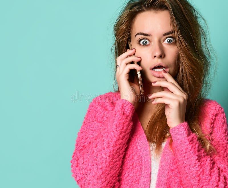 Belle jeune femme parlant par le téléphone portable sur le fond clair image stock