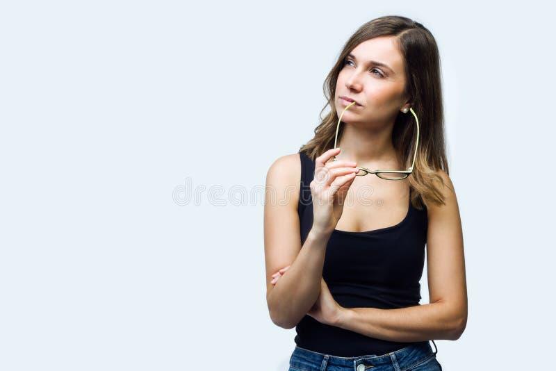 Belle jeune femme pensant sur ses inquiétudes jugeant des lunettes d'isolement sur le blanc images stock