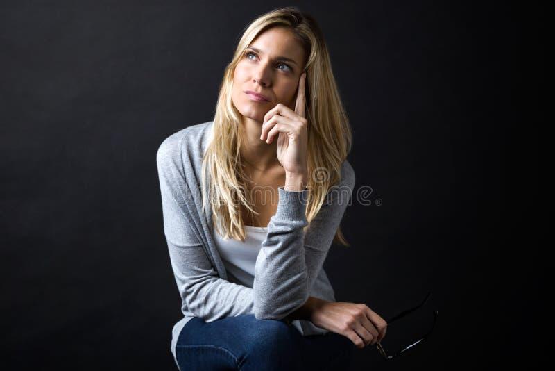 Belle jeune femme pensant sur ses inquiétudes tout en jugeant des lunettes d'isolement sur le noir photographie stock