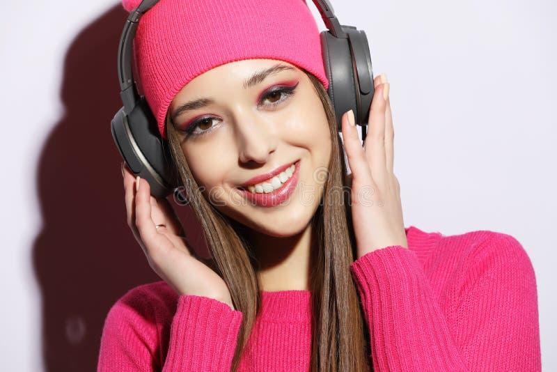 Belle jeune femme portant les vêtements roses écoutant la musique dans des écouteurs sur le fond blanc photo stock