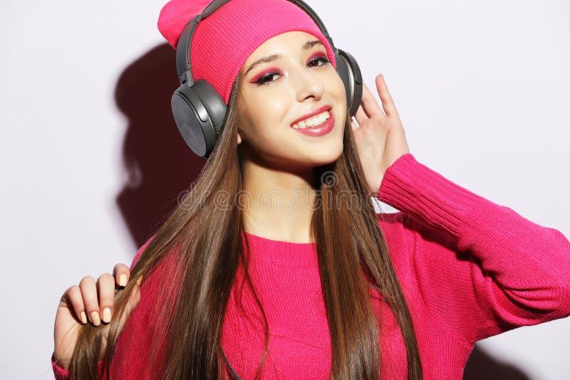 Belle jeune femme portant les vêtements roses écoutant la musique dans des écouteurs sur le fond blanc images stock