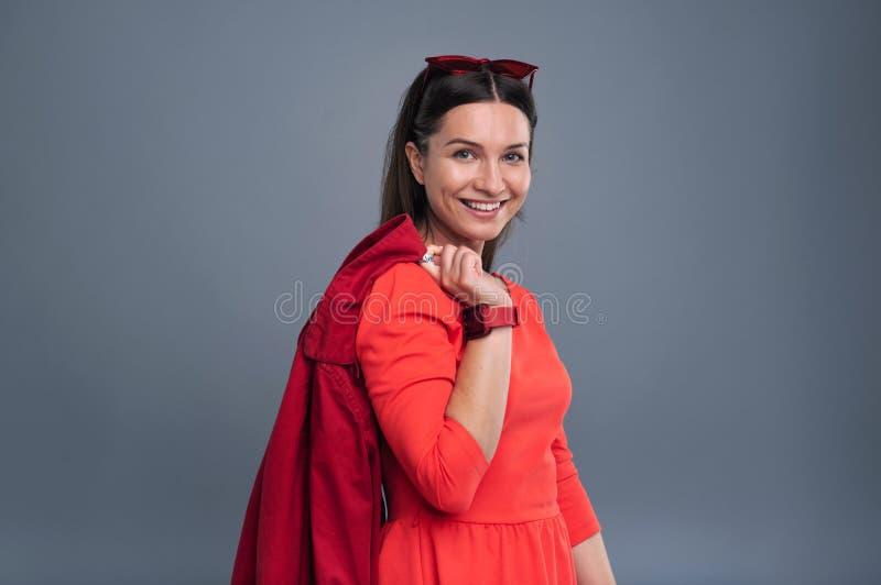 Belle jeune femme posant avec un manteau rouge photo libre de droits