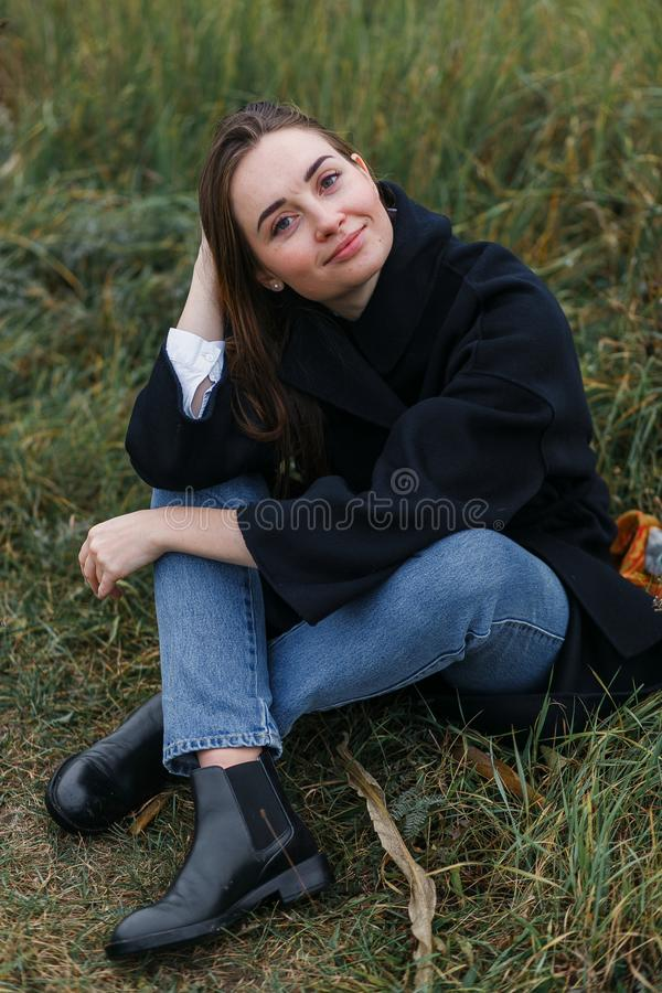 Belle jeune femme posant le sourire au-dessus du paysage pittoresque d'herbe Le mode de vie occasionnel vêtx les jeans et le mant images stock