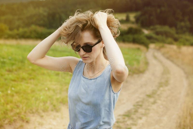 Belle jeune femme posant sur un pré photo stock