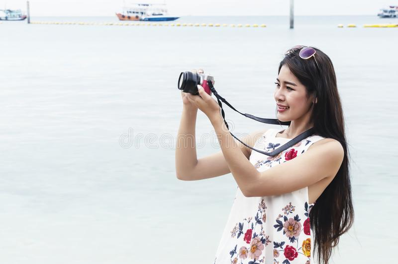 Belle jeune femme prenant la photo avec l'appareil-photo mirrorless sur la plage Mode de vie heureux d'île Ciel nuageux bleu et m photographie stock